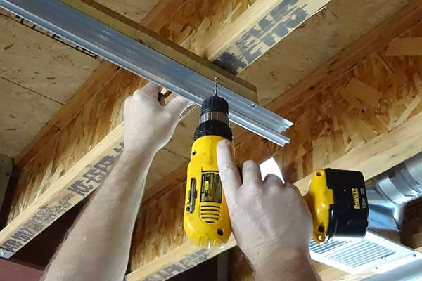 Dill holes to secure board to ceiling joists